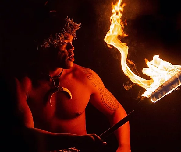 man in native garb holding firey torch - Polynesian Fire Luau