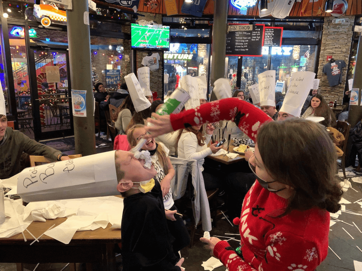 Server spraying whipped cream on boy at Dick's Last Resort