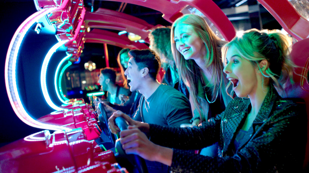 Young adults playing racing game at Dave and Buster's
