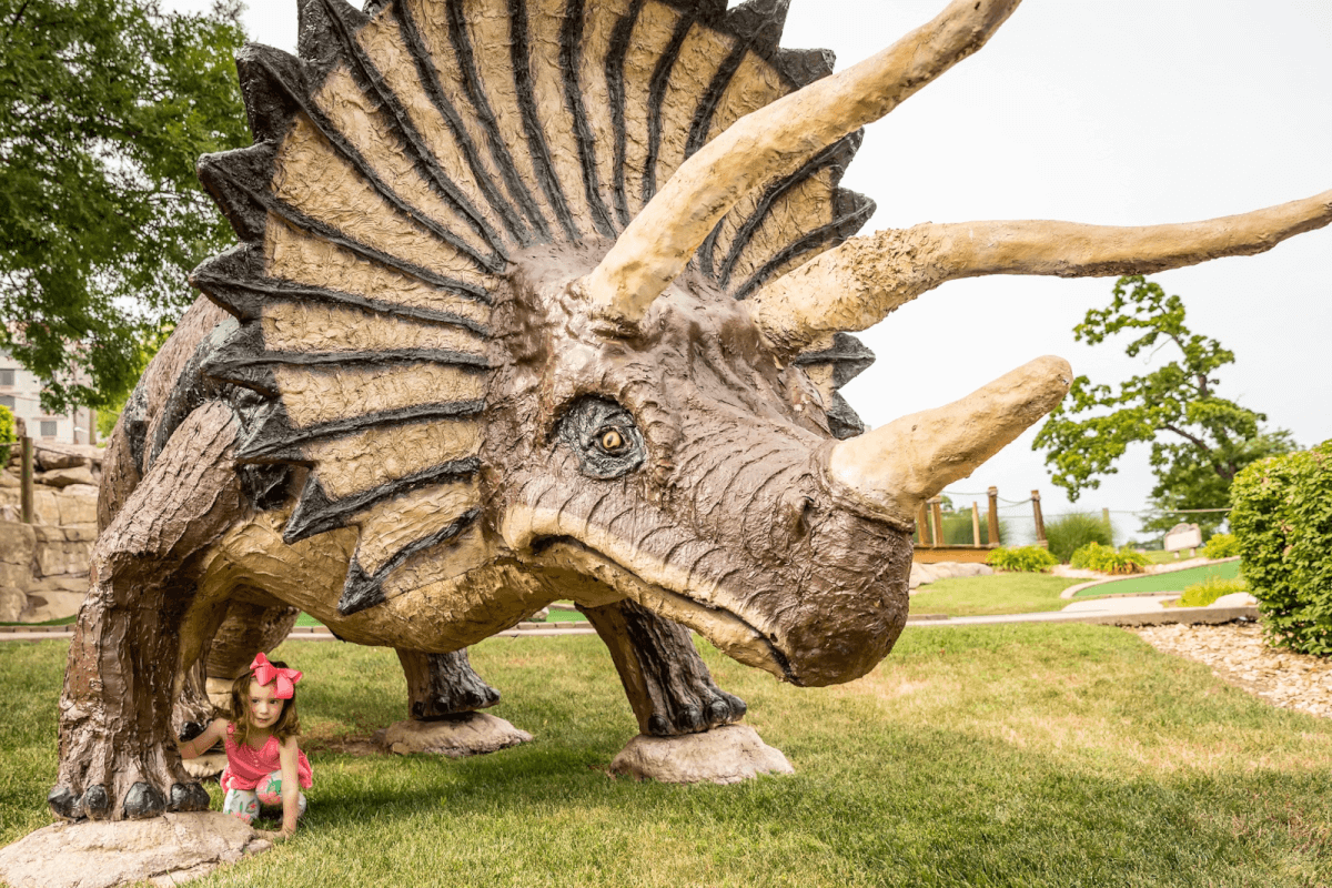 Toddler playing on triceratops statue