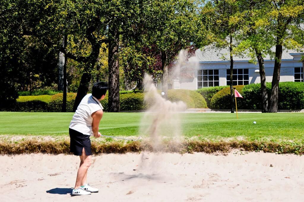 Sand flies as a golfer takes her shot - Myrtle Beach Family Golf