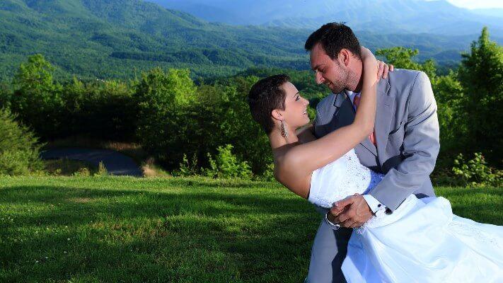 SMWA-Groom-holding-bride-mountains-background