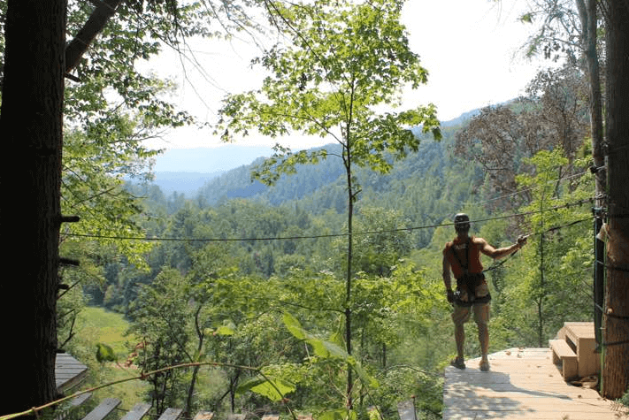 Man preparing to zipline through forest - Foxfire Mountain Adventure Park