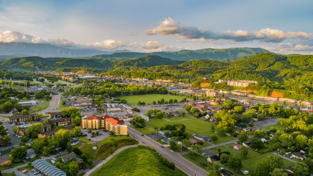 drone shot of Pigeon Forge with Smoky Mountains