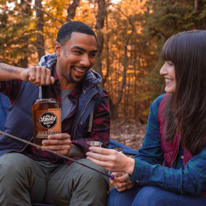 man and woman sharing Ole Smokey Whiskey outdoors