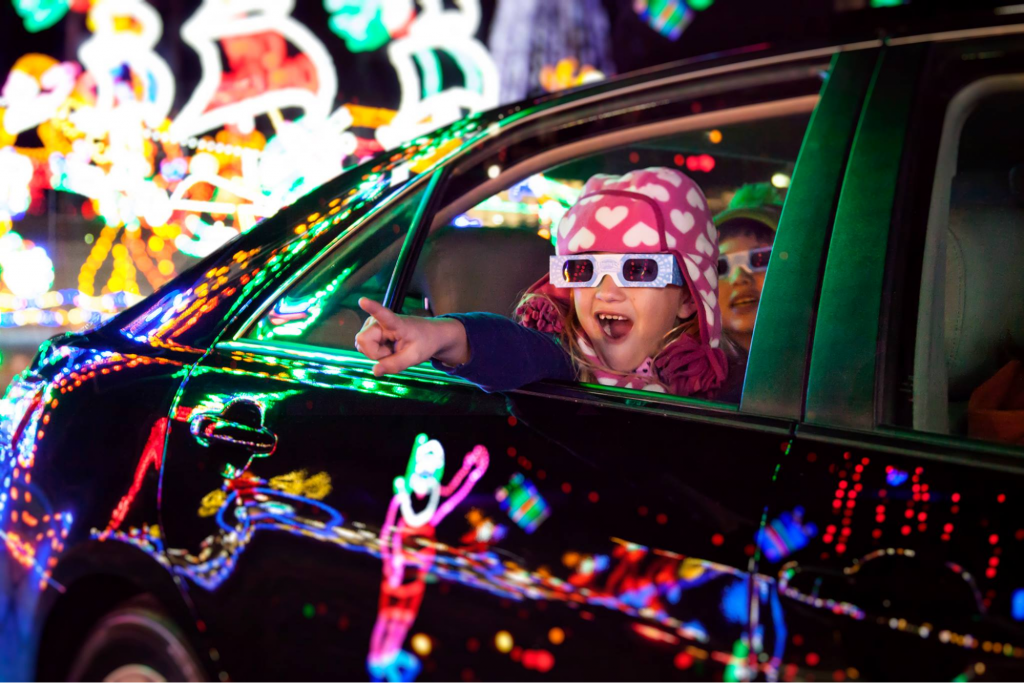 child pointing at Christmas lights
