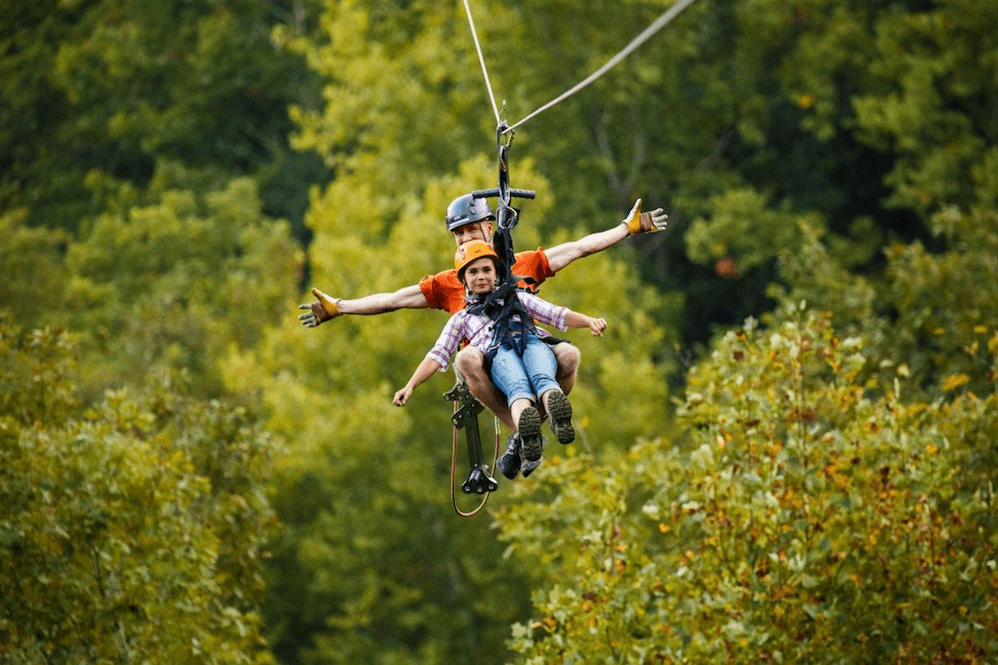 Father and daughter ziplining at Foxfire Mountain Adventure Park