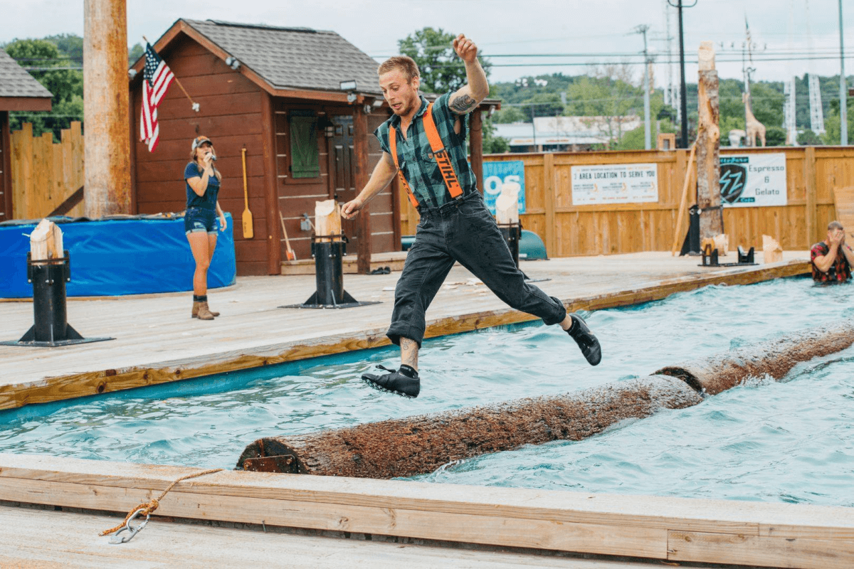 Lumberjack jumping off floating log at Paula Deen's Lumberjack Feud Show